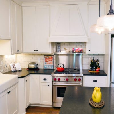 farmhouse kitchen with white cabinets, subway tile backsplash, kitchen island and farmhouse sink