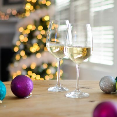 christmas ornaments and wine glasses in front of christmas tree