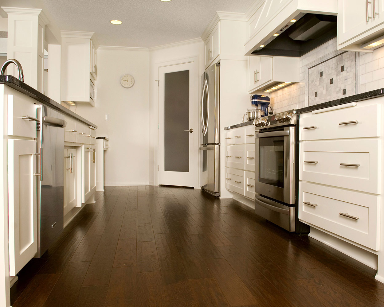 white kitchen cabinets with dark wood floor
