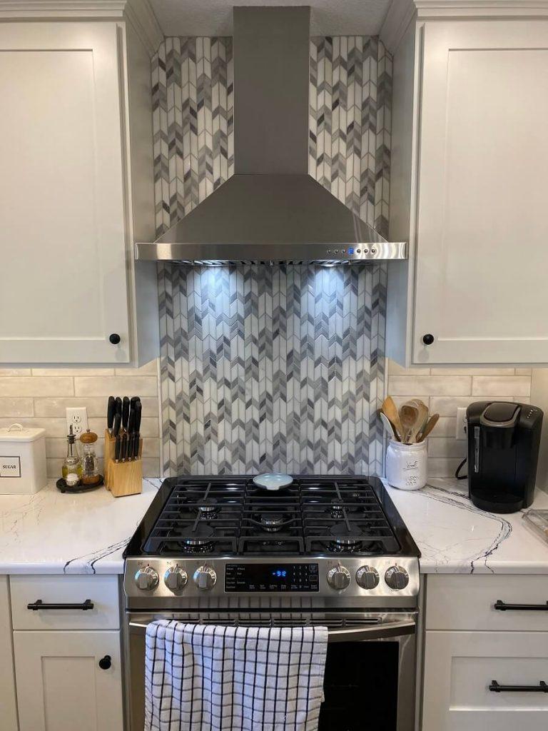 Backsplash accent with patterned tile behind stove and range hood