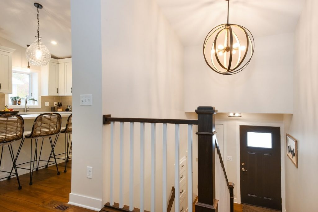 Entryway with chandelier light and white and stained railing