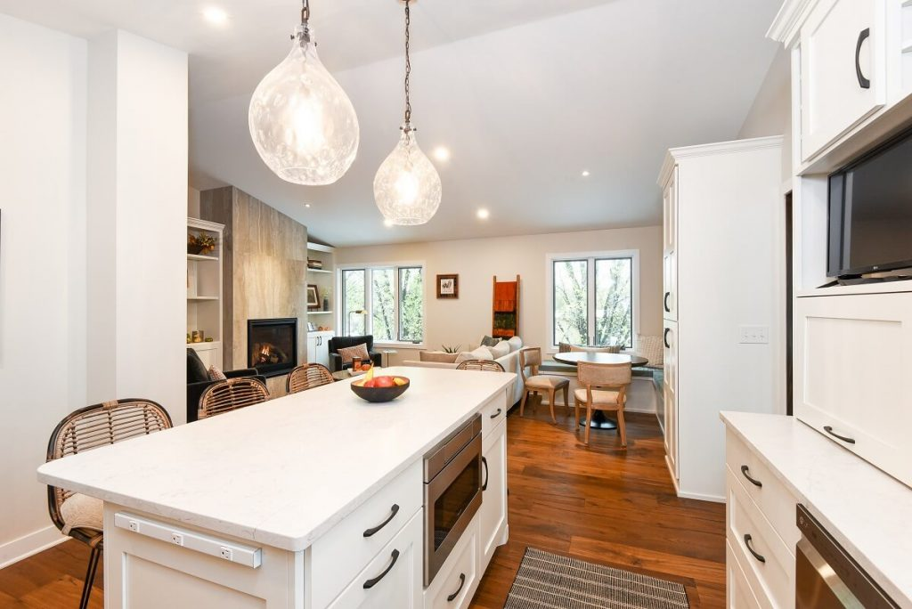White kitchen island with quartz countertops and pendant lighting