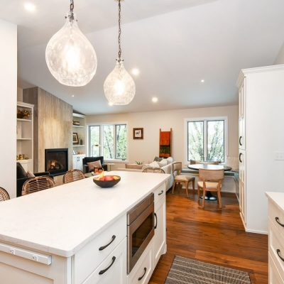 White kitchen island with quartz countertops and pendant lighting